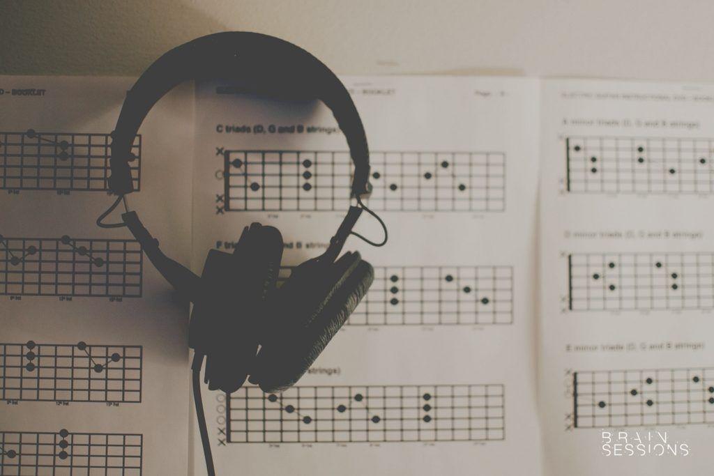 Audífonos sobre libro con cifrado americano de guitarra